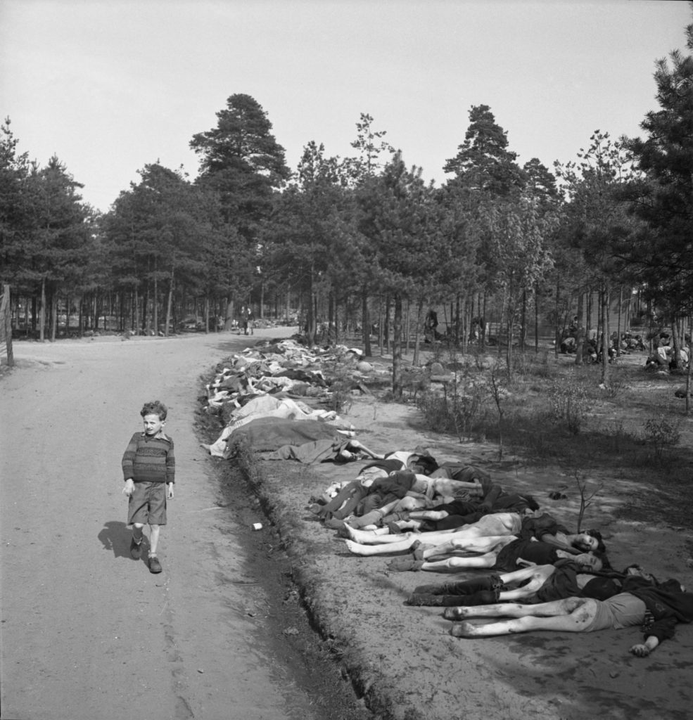 Young boy dressed in shorts walks along a dirt road lined with the corpses of hundreds of prisoners who died at the Bergen-Belsen extermination camp, near the towns of Bergen and Celle, Germany, April 20, 1945. (Photo by George Rodger/The LIFE Picture Collection via Getty Images)